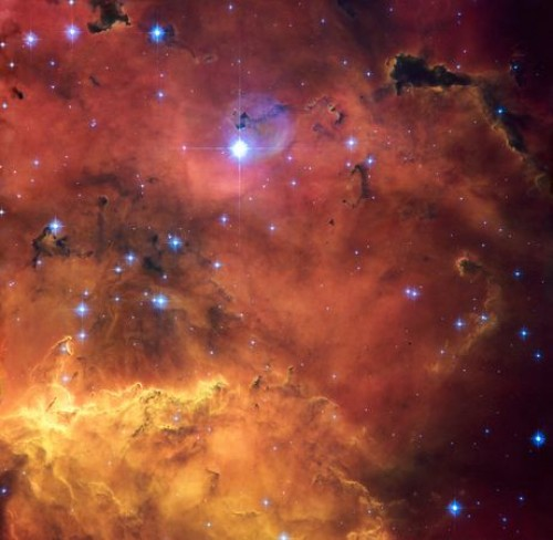 A colourful star-forming region is featured in this Hubble Space Telescope image. Looking like a roiling cauldron of some exotic cosmic brew, huge clouds of gas and dust are sprinkled with bright blue, hot young stars.