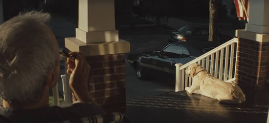Clint Eastwood smoking a cigarette on his porch admiring his Gran Torino